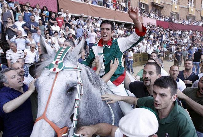 Победители первого этапа Палио 2013 в Сиене: наездник Джованни Атцени и его скакун Гуэсс